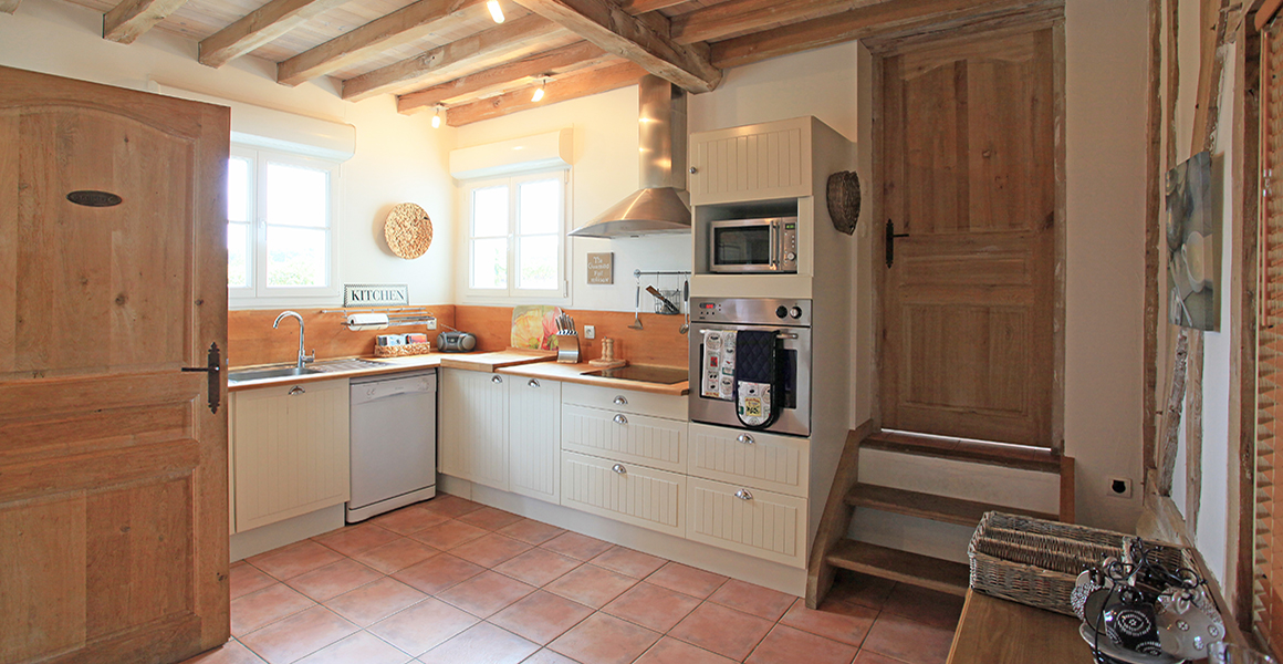 The well equipped kitchen with steps up to the utility room