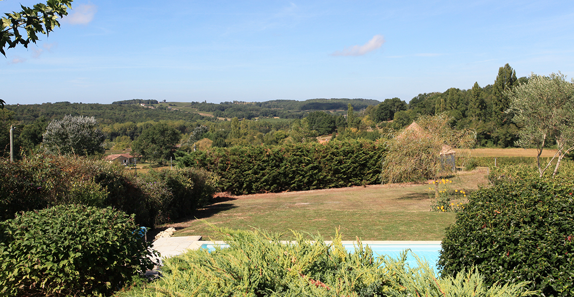 The view from the terrace across the pool and garden
