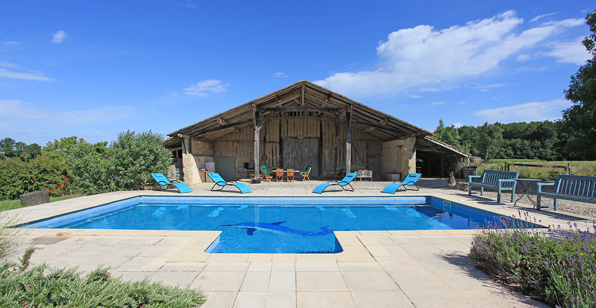The pool with open barn behind, with covered seating area, table tennis and games