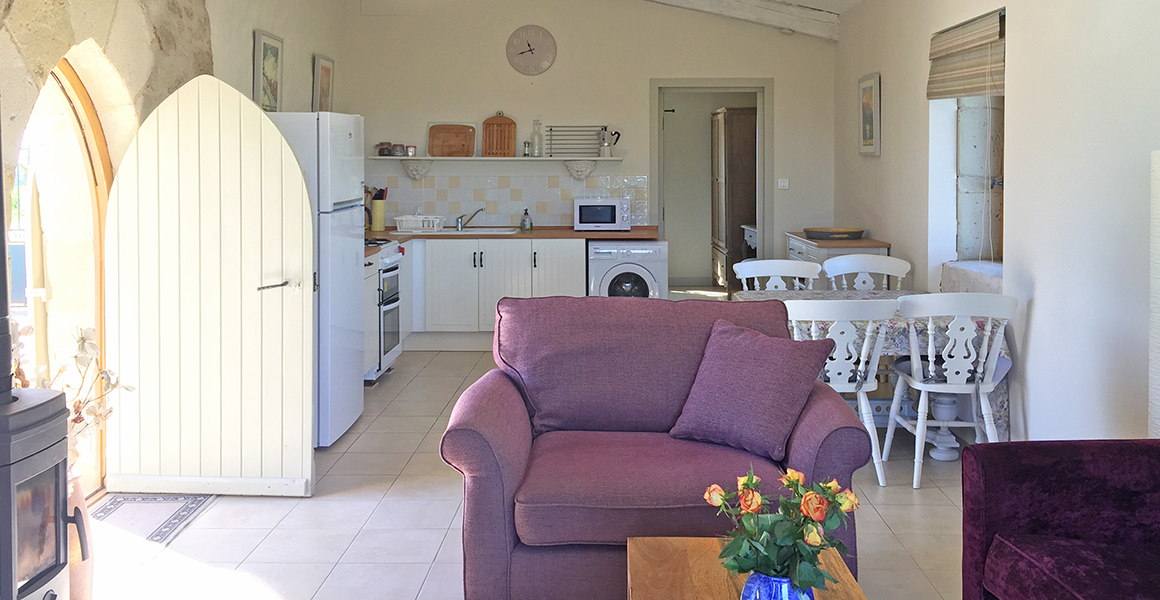 Comfortable gite living area with well equipped kitchen and door through to en suite bedroom