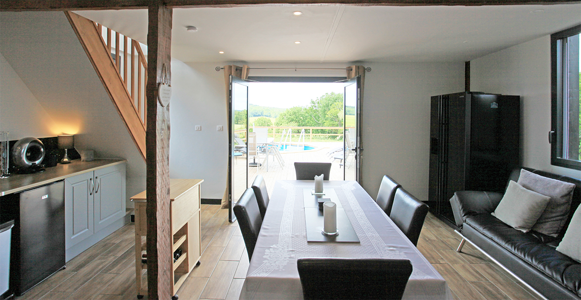 The kitchen dining area opens out onto the large decked terrace and pool